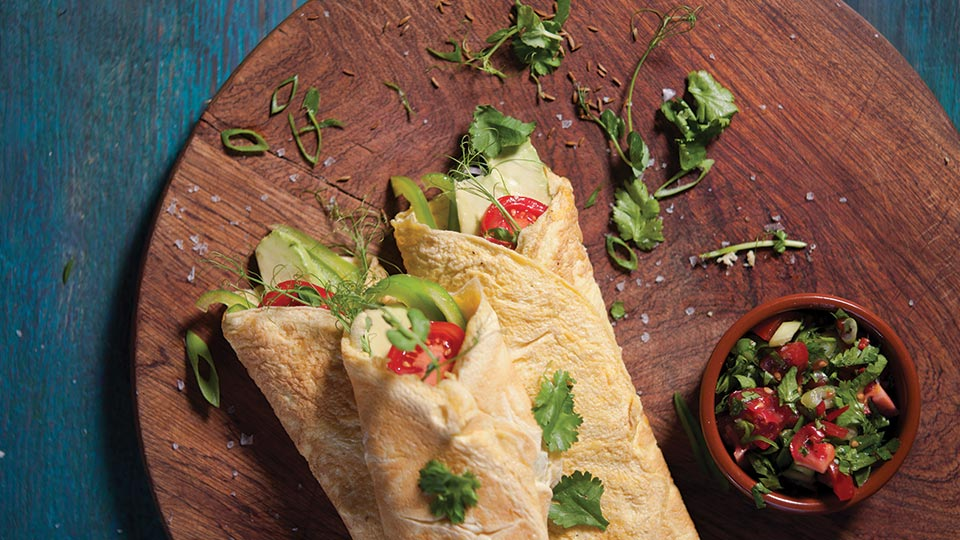 healthy egg burritos on wooden chopping board