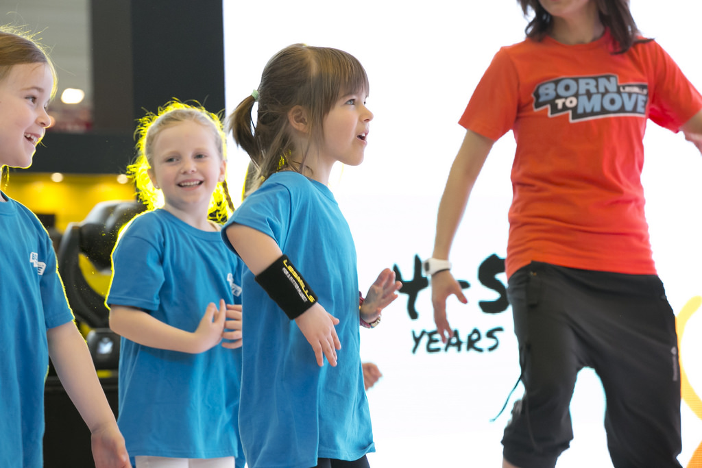 Three children doing an exercise class