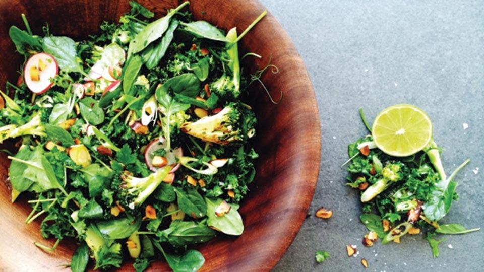 broccoli spinach radish salad in a wooden bowl