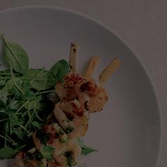 Garlic prawn skewers on a plate