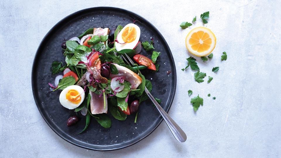 Nicoise salad on a plate with an orange
