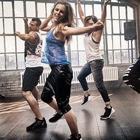 Women having fun dance move fitness class.
